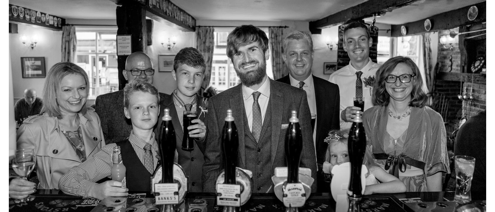 A handsome groom surrounded by his loving family with a setting of a stunning bar.