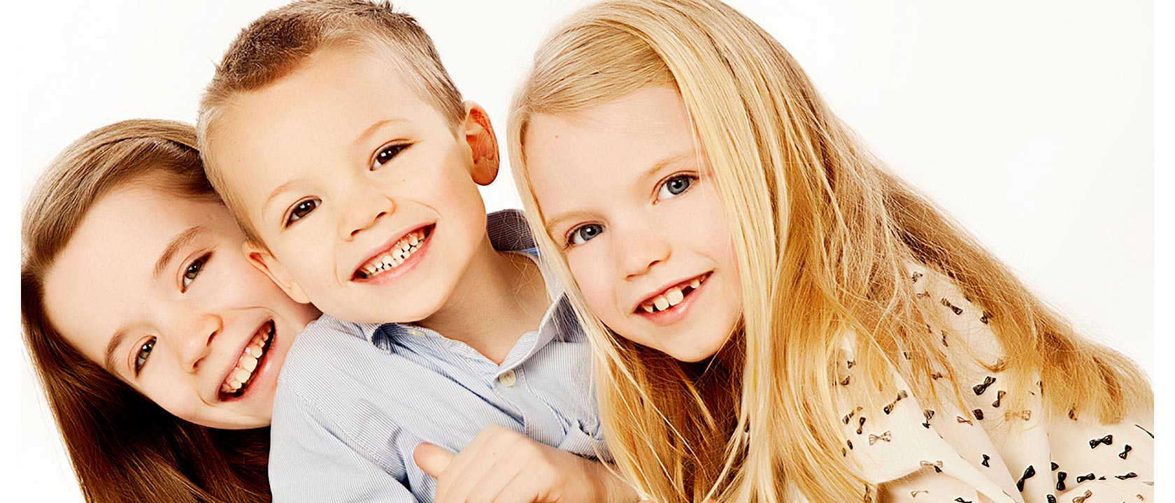 A photography of three happy siblings taken at our Midlands Photography Studio