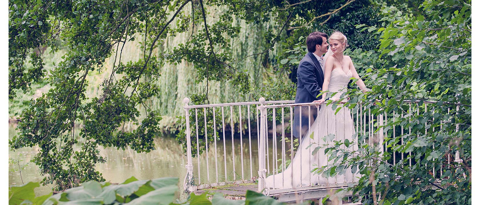 A bride and her handsome groom standing on an ornate garden bridge.